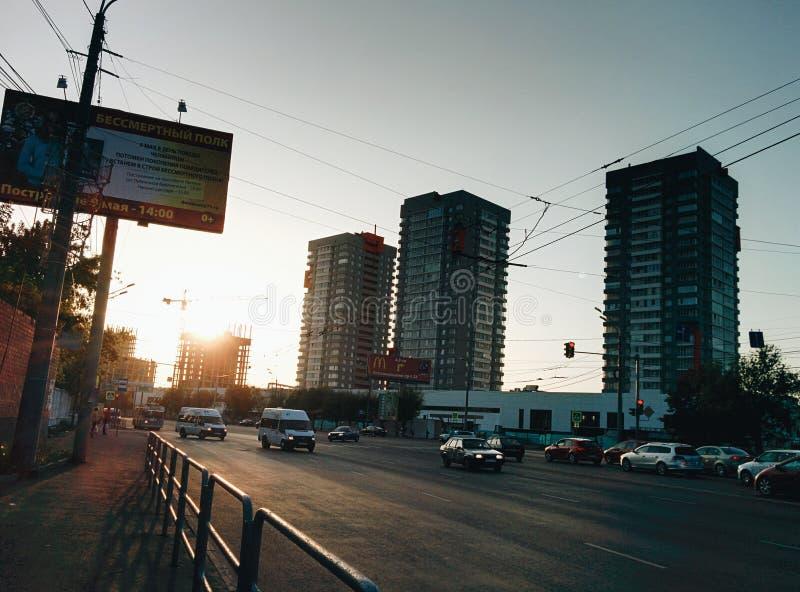 Chelyabinsk stadsväg i solnedgång med bilar och byggnader arkivbild