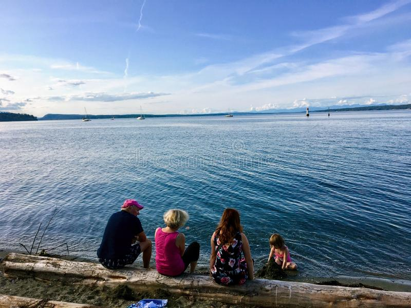 A family of three generations sitting on a log enjoying the beach admiring the beautiful vast ocean in Chemainus, B.C., Canada. stock image