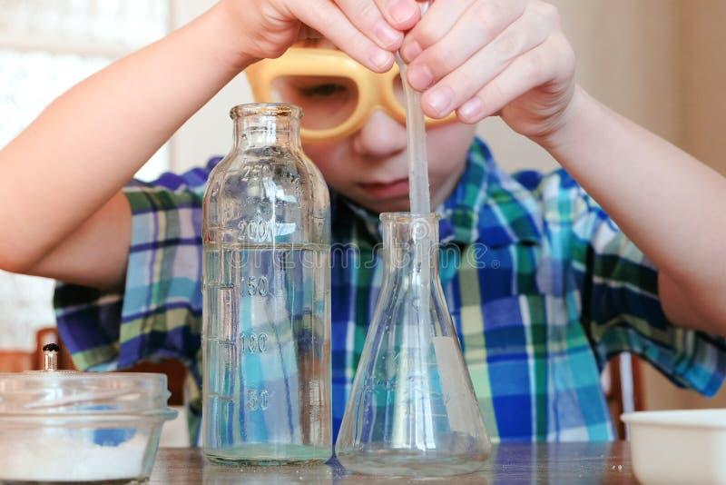 Chemia eksperymentuje w domu Chłopiec nalewa wodę od butelki w kolbę używać pipetę fotografia stock