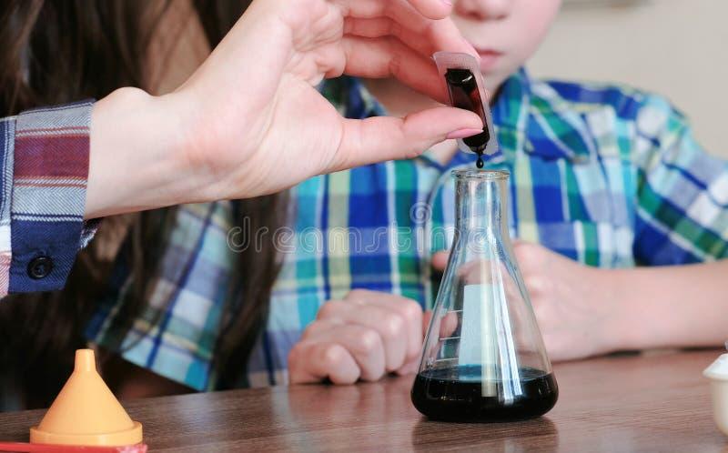 Chemia eksperymentuje w domu Kobieta kapie farbę w kolbę z cieczem fotografia stock