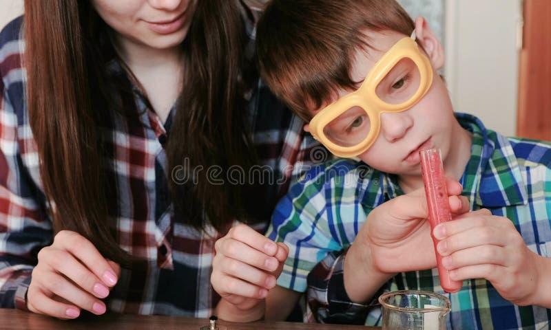 Chemia eksperymentuje w domu Mama i syn robimy chemicznej reakci z uwolnieniem gaz w próbnej tubce z czerwienią obraz royalty free
