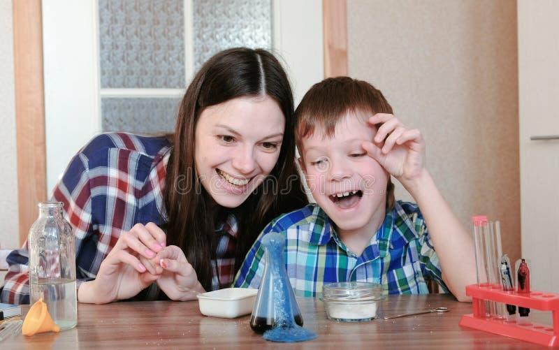 Chemia eksperymentuje w domu Szczęśliwa mama i syn robimy chemicznej reakci z uwolnieniem gaz w kolbie obrazy royalty free