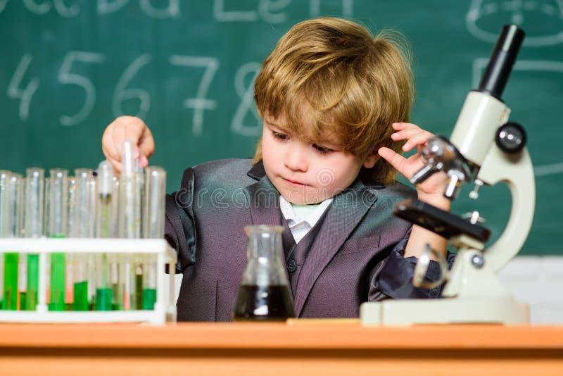 Chemical analys Litet barnsnille behandla som ett barn Pojkebruksmikroskop och provrör i skolaklassrum Retro laboratoriumutrustni arkivfoton