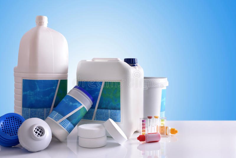 Chemical cleaning products for pool with blue background. Chemical cleaning products for pool water on white table and blue background. Horizontal composition stock photo