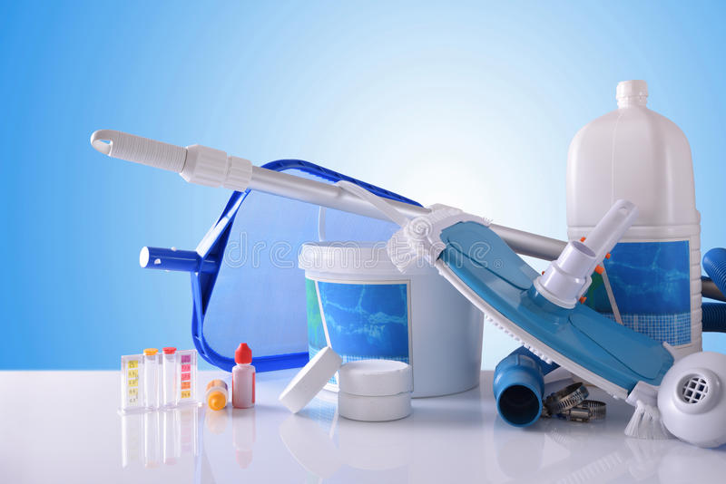 Chemical cleaning products and tools for pool with blue background. Chemical cleaning products and tools for pool water on white table and blue mosaic background royalty free stock photography