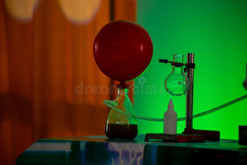 Test tube on a tripod, gas from a test tube with liquid inflates a red balloon stock image