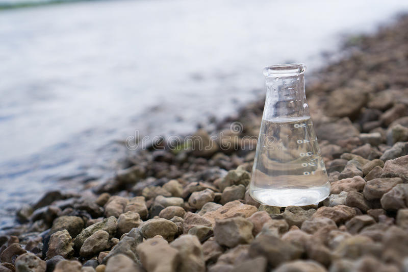 Chemical flask with water, lake or river in the background. stock photos