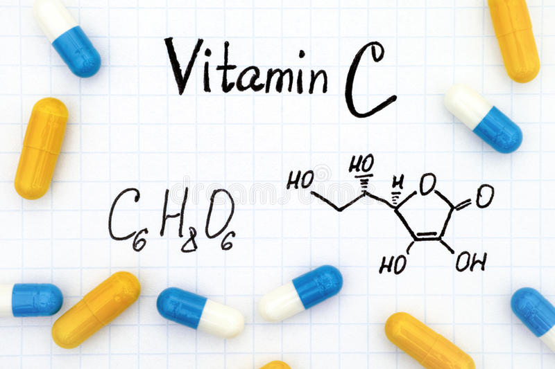 Chemical formula Vitamin C and pills. stock image