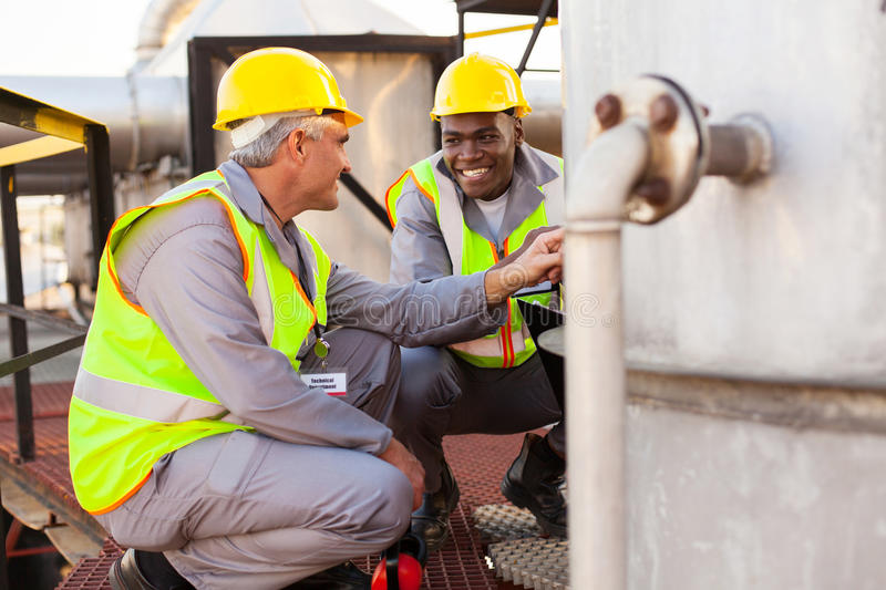 Chemical industry technicians. Two oil chemical industry technicians working in plant stock photos