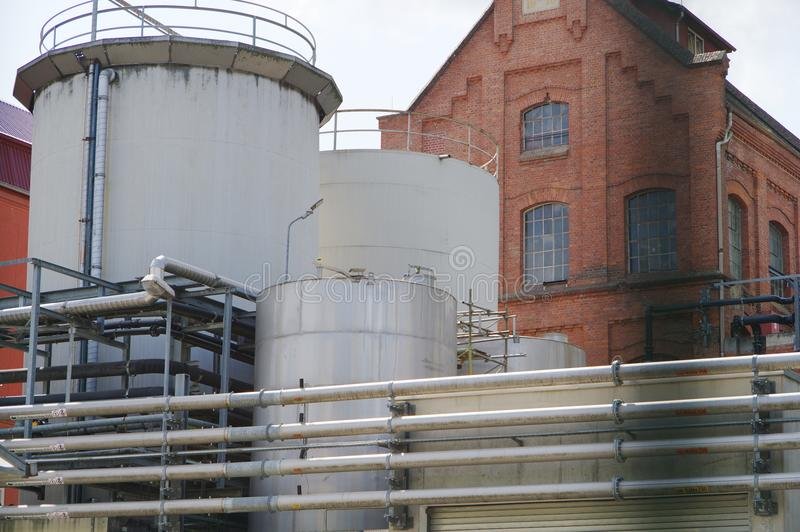 Chemical plant with modern production and old brick factory building. Old factory building from brick wall, large round tank behind stainless steel Piping stock image