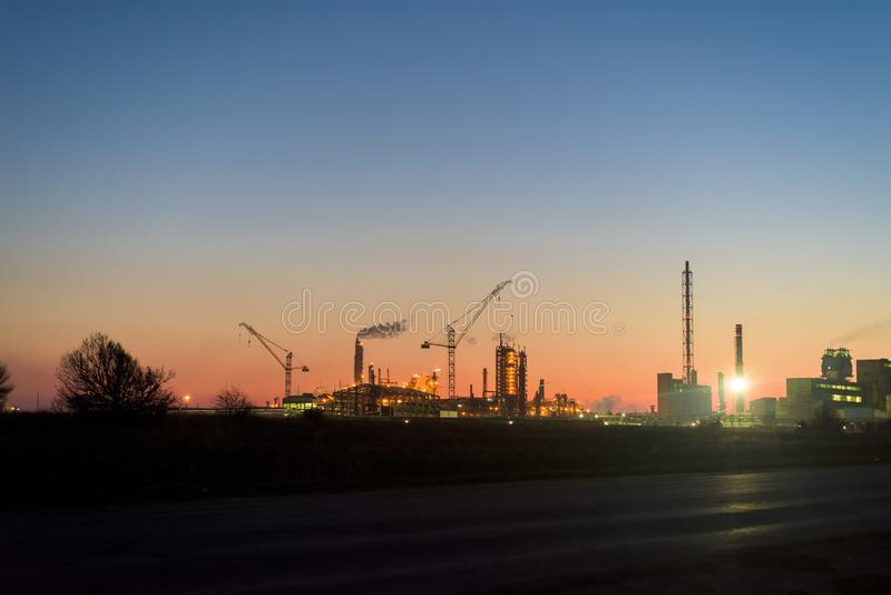 Chemical plant in a silhouette image at sunset, the glowing light of the chemical industry at sunset and twilight sky, the field royalty free stock image