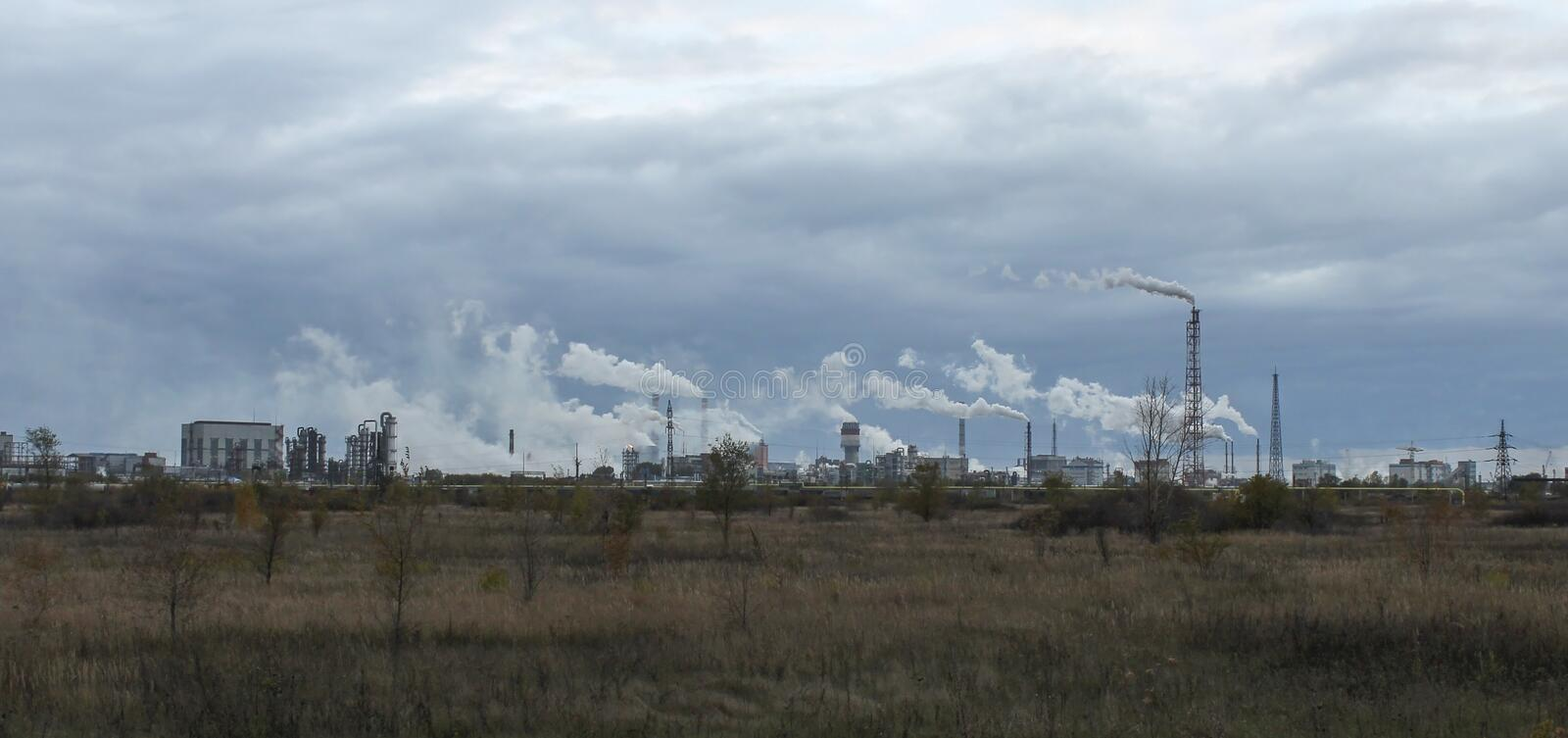 Chemical plants in Togliatti. Industrial zone with factories and pipes with smoke and illumination at cloudy day royalty free stock photo