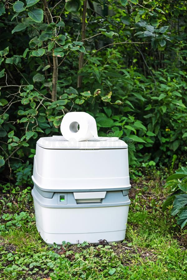 Chemical portable toilet. Single portable toilet standing on green nature courtyard background. Chemical portable toilet and toilet paper roll. Single portable royalty free stock image
