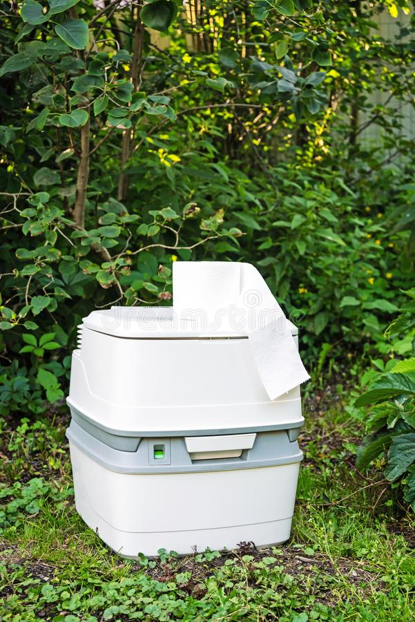 Chemical portable toilet. Single portable toilet standing on green nature courtyard background. Chemical portable toilet and toilet paper roll. Single portable royalty free stock photos