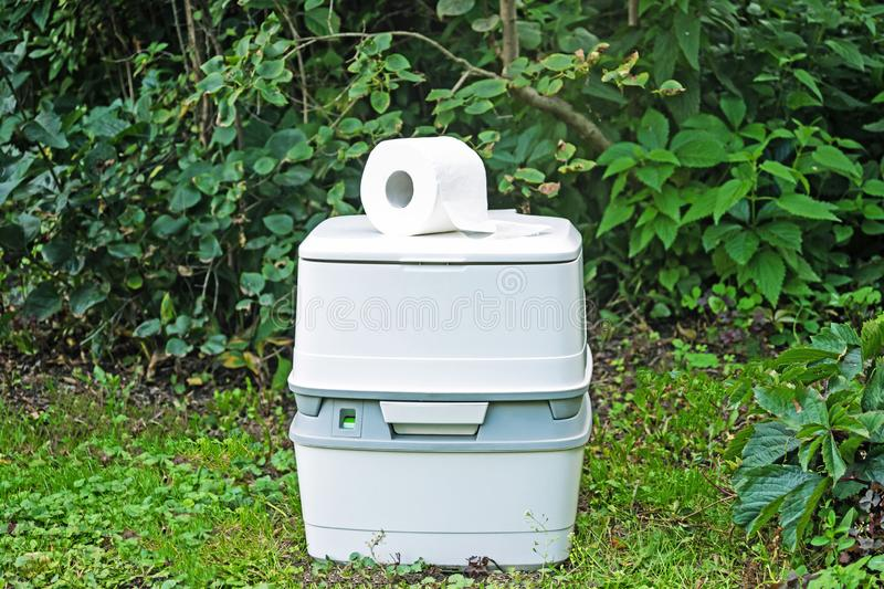 Chemical portable toilet. Single portable toilet standing on green nature courtyard background. Chemical portable toilet and toilet paper roll. Single portable stock image