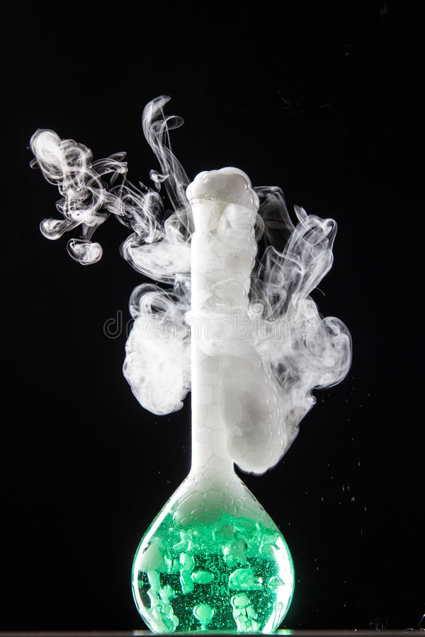Chemical reaction in volumetric flask glass in labolatory royalty free stock photography