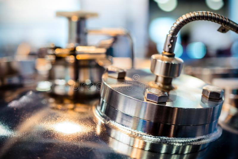 Chemical reactor body, selective focus. Metal flanges with flexible nipples. Abstract industrial background stock image