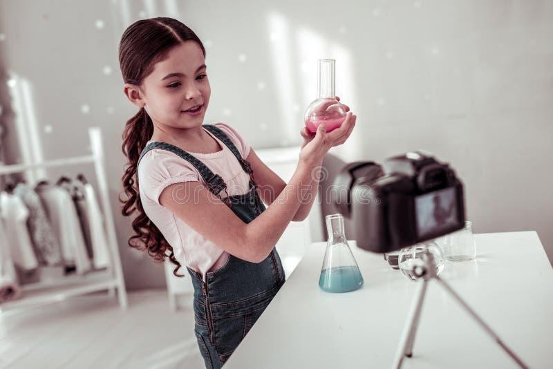 Joyful intelligent girl holding a small flask royalty free stock photo