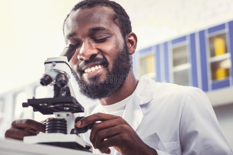 Chemical student enjoying his time working with microscope. Enjoying time. Clever chemical student feeling satisfied enjoying his time while working with modern royalty free stock image
