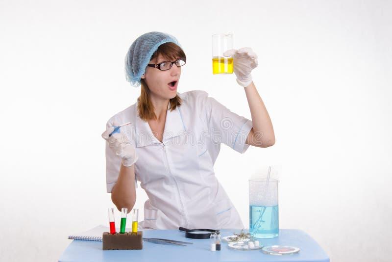 Chemicus die de vloeistof in fles bekijken stock afbeeldingen
