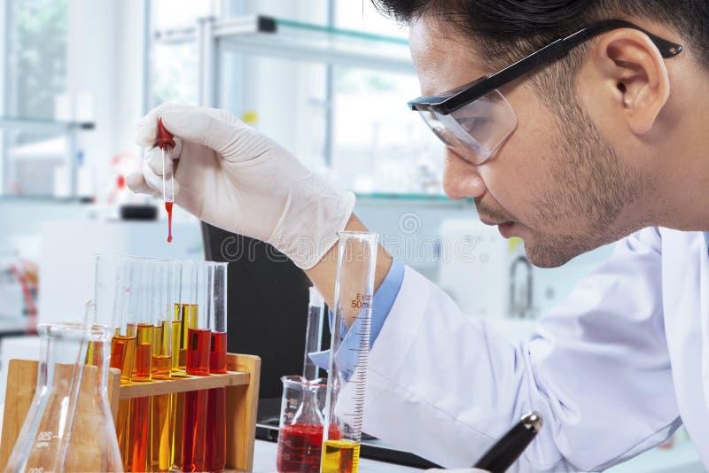 Chemicus die onderzoek met chemische vloeistof doen royalty-vrije stock foto