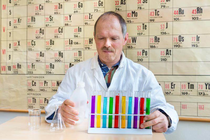 Chemieleraar die kleurrijke reageerbuizen vullen stock foto