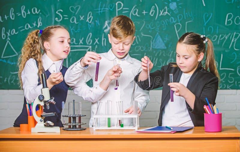 Chemiemikroskop Kleinkinder, die Chemie im Schullabor lernen Studenten, die Biologieexperimente mit Mikroskop tun stockbilder