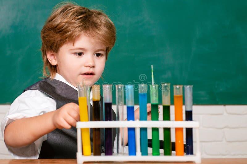 Chemii nauka pierwszy dzie? szko?y Szczęśliwy mały naukowiec robi eksperymentowi z próbną tubką nauka w domu lab obrazy stock