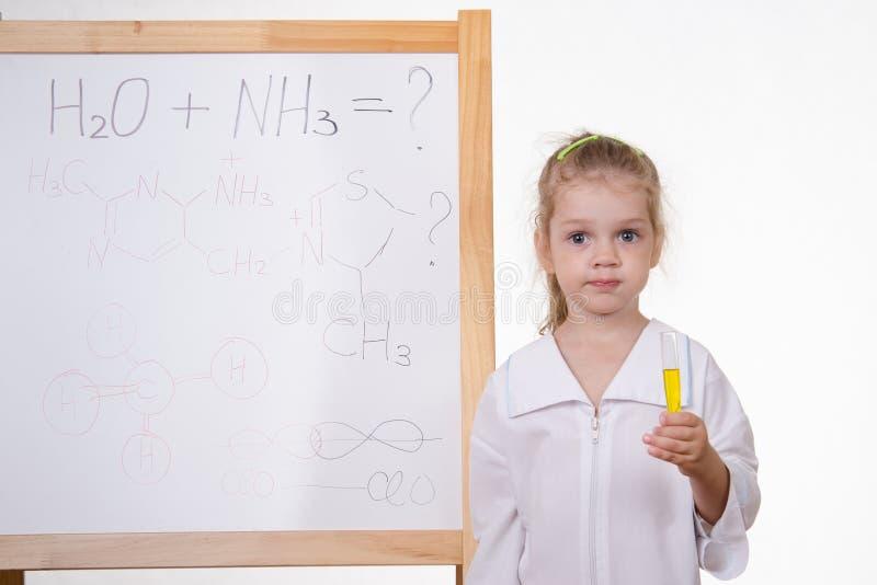 Chemiker mit Reagenzglas an der Tafel lizenzfreies stockfoto