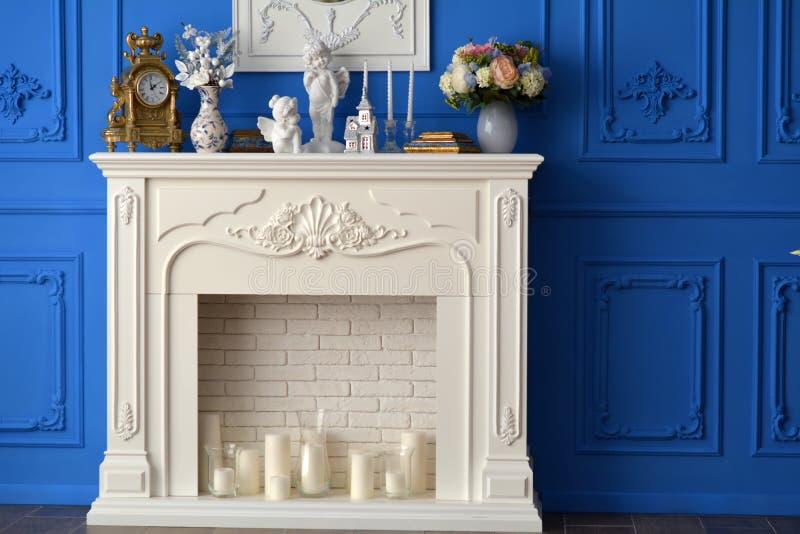 Cheminée blanche avec un miroir dans la chambre, sur les montres d'étagère, souvenirs, bougies photo stock