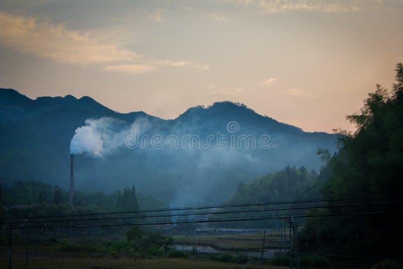 Cheminée d'évacuation des fumées et lignes électriques en Chine rurale images libres de droits