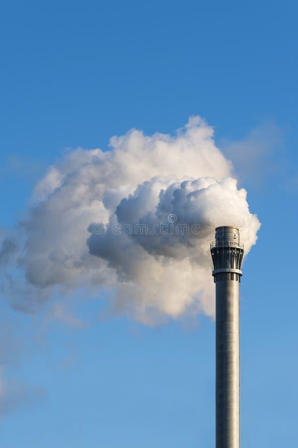 Cheminée d'industrie avec des nuages de fumée contre le ciel bleu, copie photographie stock libre de droits