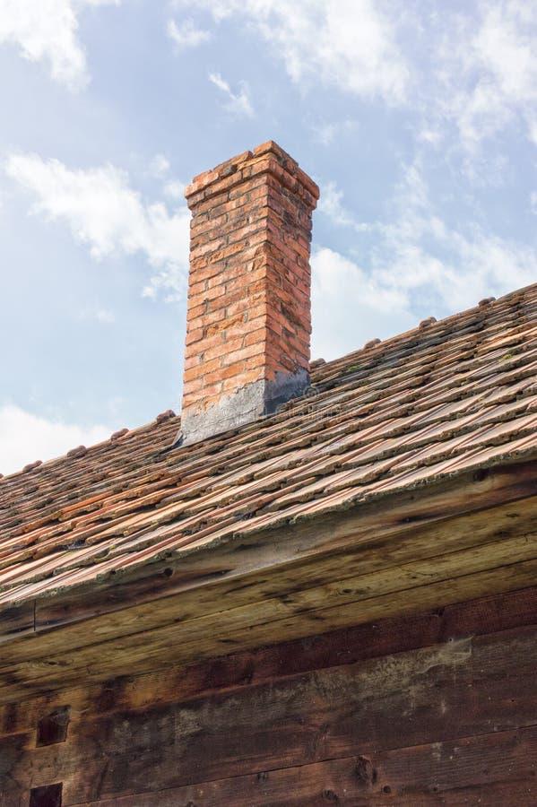 Cheminée de brique sur le toit de tuile d'une vieille maison en bois photos stock