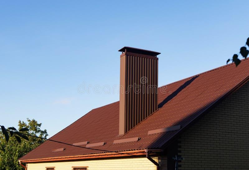 Cheminée de recouvrement Profiled sur le toit de tuile en métal avec des gouttières de pluie et des gardes de neige image libre de droits