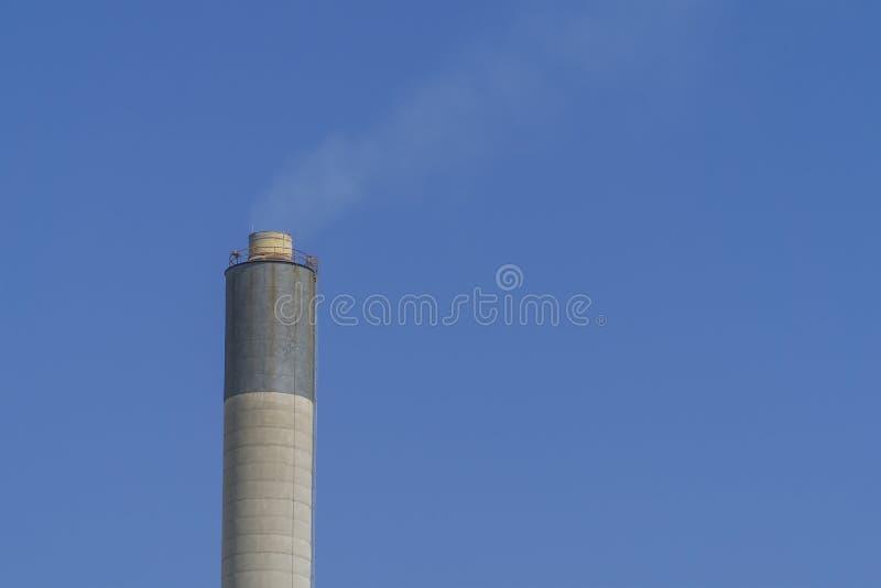 Cheminée et fumée industrielles avec le fond de ciel bleu image libre de droits