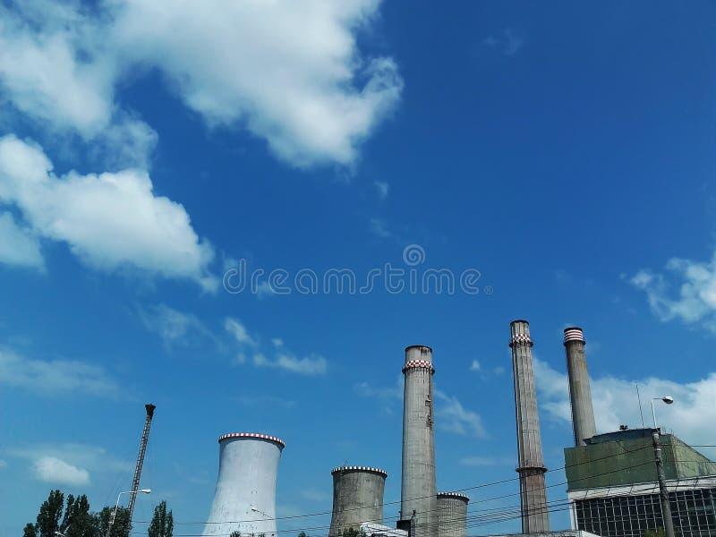 Cheminée industrielle contre le ciel nuageux bleu images stock