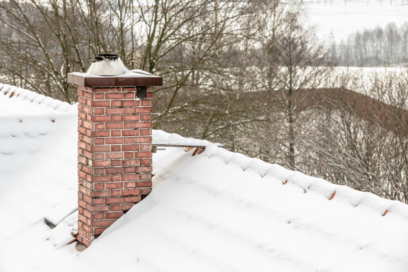 Cheminée rouge et toit couverts de neige photos libres de droits