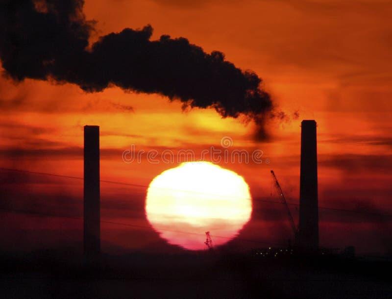 Cheminées d'évacuation des fumées contre le ciel rouge photos stock
