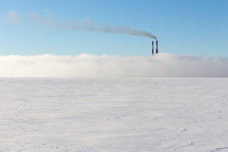 Cheminées dans la brume sur le lac congelé image stock