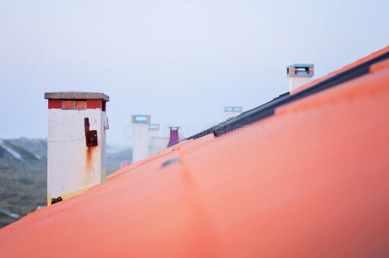 Cheminées dans une rangée sur Clay Tiles Rooftop rouge photos stock