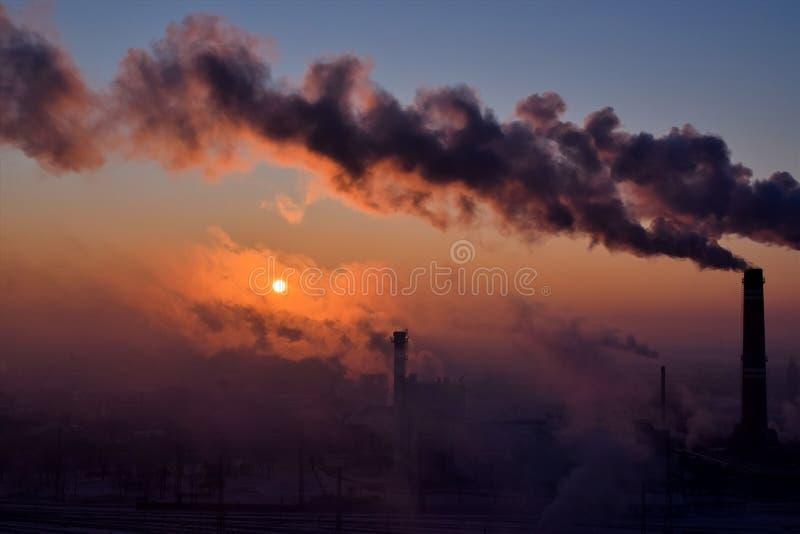 Cheminées de tabagisme au lever de soleil images libres de droits