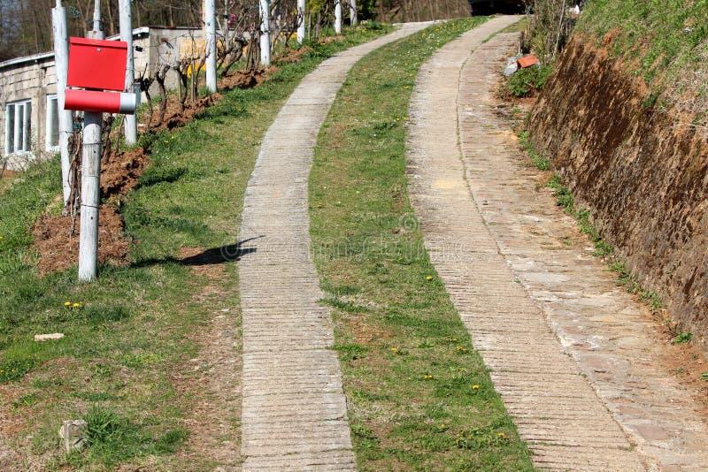 Chemin ascendant dans la zone rurale faite en tuiles en pierre et herbe entourées avec la boîte aux lettres et les usines photos libres de droits