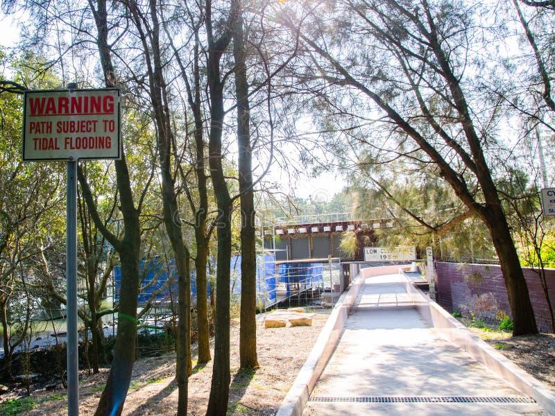 Chemin carré de ` de panneau d'avertissement sujet au ` de marée d'inondation dans un jardin images stock