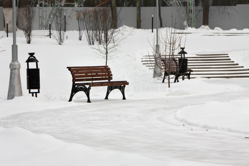 Chemin circulaire de désert avec des bancs de jardin en parc d'hiver photos stock