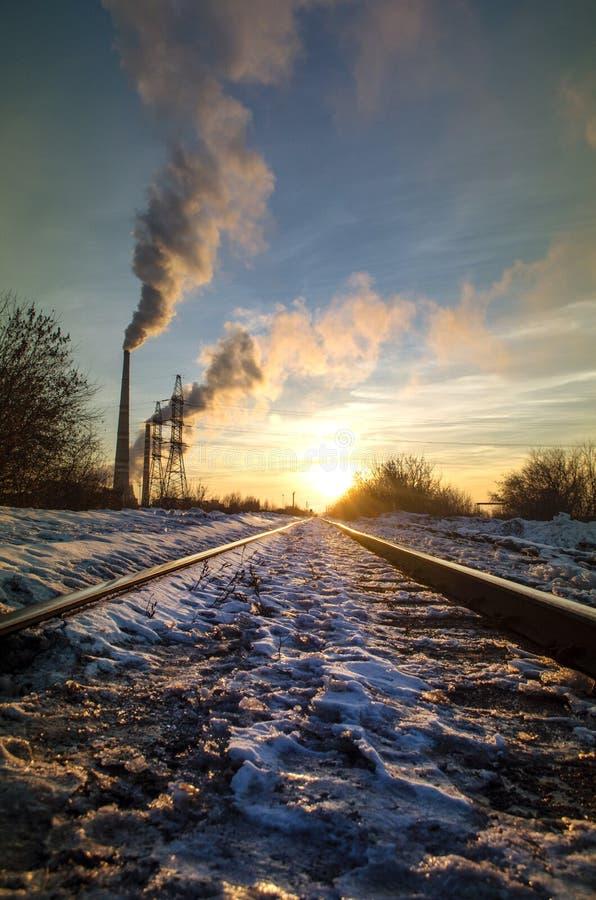 Chemin de fer d'hiver à l'usine dans des rayons de coucher du soleil photo libre de droits