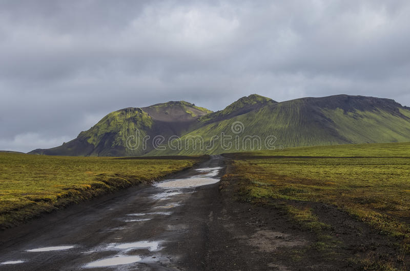 Chemin de terre après pluie et montagnes volcaniques couvertes de mousse Landma photographie stock libre de droits