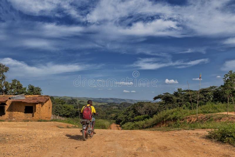 Chemin de terre avec le motocycliste africain, zone rurale de l'Afrique de malange, Angola photo stock