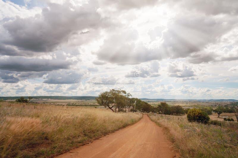 Chemin de terre de campagne parmi des champs avec le soleil par des nuages images libres de droits
