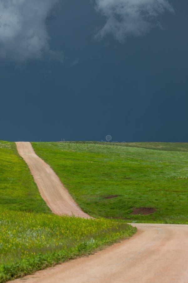 Chemin de terre en soleil avec la temp?te image libre de droits