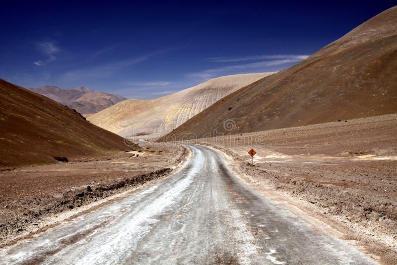 Chemin de terre de enroulement menant dans la vallée aride avec les collines jaunes et brunes sèches stériles dans le désert d'At image stock